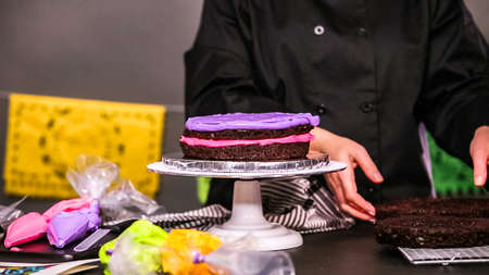 Step by step. Baker assembling a chocolate cake with bright colorful buttercream frosting for  holiday. Stok Fotoğraf