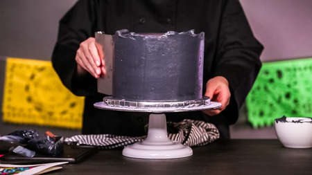 Step by step. Baker frosting multilayer chocolate cake with a black italian buttercream frosting.
