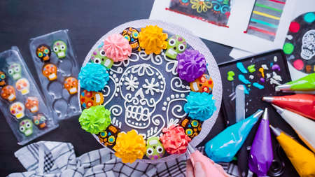 Step by step. Flat lay. Baker decorating multilayer chocolate cake with colorful italian buttercream frosting.