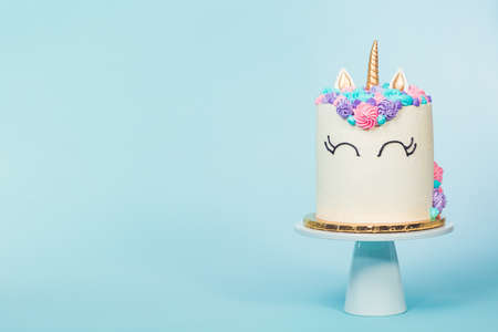 Gourmet unicorn cake with pink and purple buttercream frosting on blue background. Imagens