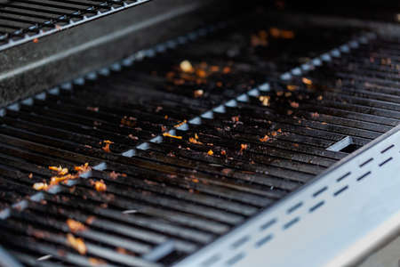 Dirty cast iron cooking grates on outdoor gas grill.