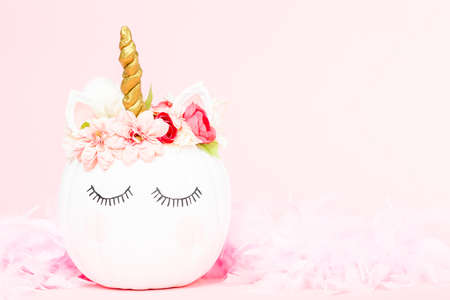 White unicorn pumpkin decorated with flowers on a pink background.