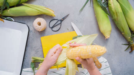 Shucking organic corn to make Mexican corn on the cob Elote. 版權商用圖片