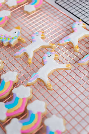 Decorating unicorn themed sugar cookies with royal icing.