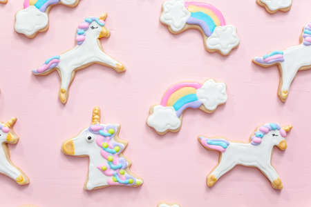 Unicorn sugar cookies decorated with royal icing on a pink  background. Reklamní fotografie