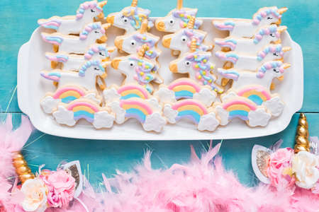 Unicorn sugar cookies decorated with royal icing on a blue background.