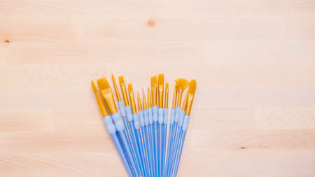 variety of new paint brushes with paint on a wood table. Фото со стока