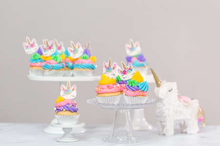 Unicorn cupcakes with multicolor buttercream icing on cake stands.