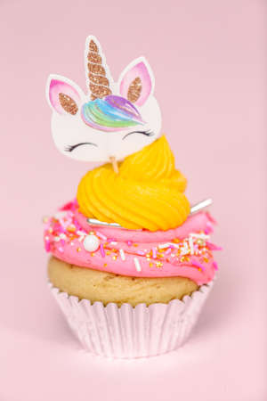 Fancy unicorn cupcakes with multicolor buttercream icing and unicorn cupcake topper on pink background. Stock Photo