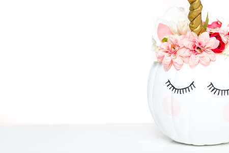 Craft pumpkin painted white and decorated with pink flowers as unicorn on white background. Stock Photo