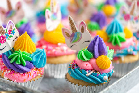 Unicorn cupcakes with multicolor buttercream icing on metal tray.