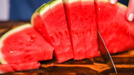 Slicing red woatermelon on a wood cutting board. Stock Photo
