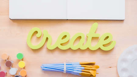 Green create sign with paint brushes on the table.