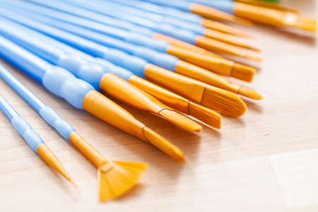 variety of new paint brushes with paint on a wood table. Stock Photo