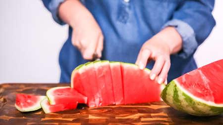 Slicing red woatermelon on a wood cutting board. Фото со стока