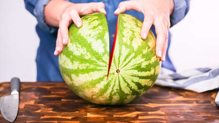 Slicing red woatermelon on a wood cutting board.
