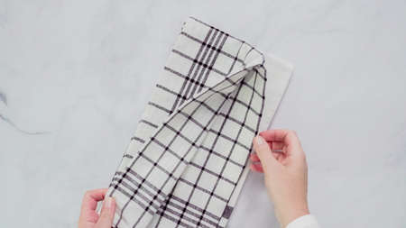 Folding Blck and white patterned paper towels on marble surface.