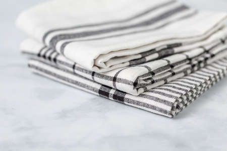 New kitchen towels with simple black pattern folded on marble counter.