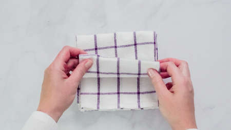 Folding blue and white patterned paper towels on marble surface.