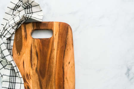 Rustic wood cutting board on marble countertop.