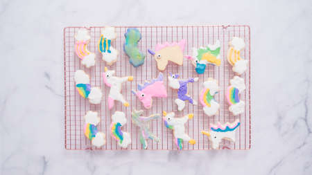 Unicorn cookies decorated with royal icing drying on drying rack. Archivio Fotografico