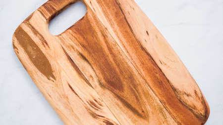 Rustic wood cutting board on marble kitchen counter.