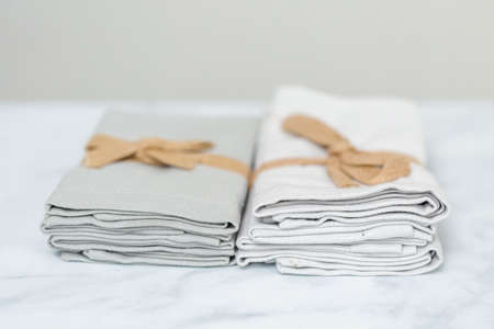 Stack of new linen dinner napkin on the kitchen counter.