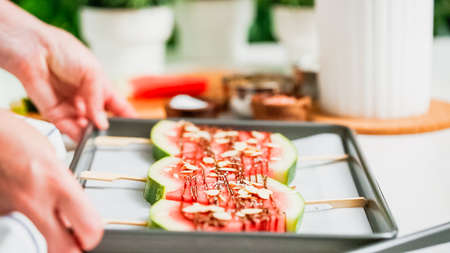 Step by step. Garnishing watermelon ice pops with sea salt, almons and coconut. Stockfoto