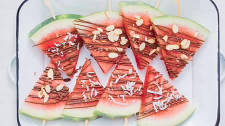Step by step. Watermelon wedges garnished with chocolate and sea salt  on the stick on metal serving tray.