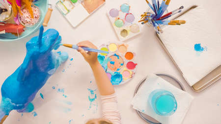 Step by step. Painting paper mache unicorn with blue paint. 版權商用圖片 - 112175844