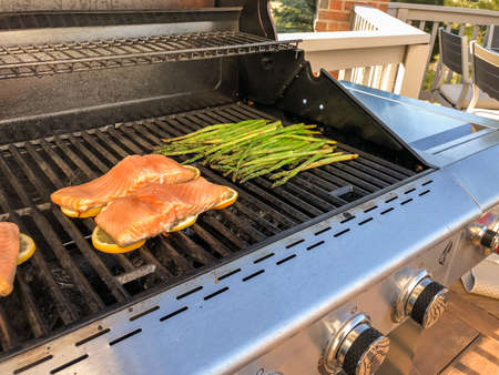 Step by step. Grilling salmon with lemons on outdooor gas grill. Foto de archivo