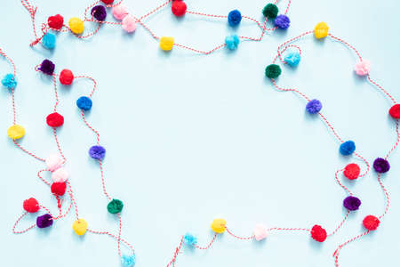 Pom pom colorful party garland on blue backgrouns.