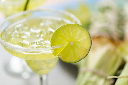 Lime margaritas on the rocks garnished with fresh slice of lime.
