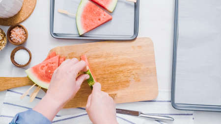 Step by step. Sliding the wood pop stick into the watermelon wage wedge to make watermelon ice pops. Banco de Imagens - 112174911
