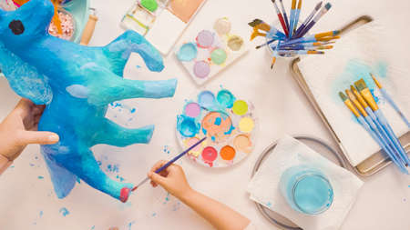 Step by step. Painting paper mache unicorn with blue paint.