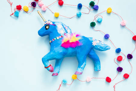 Kids craft. Painted blue and decorated with jewels and feathers paper mache unicorn. Stock Photo