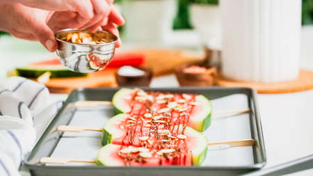 Step by step. Garnishing watermelon ice pops with sea salt, almons and coconut. Stock Photo