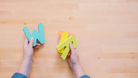 Word WRITE from multicolor wooden letters on wooden table.