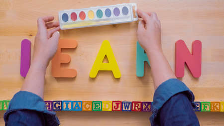 Word LEARN from multicolor wooden letters on wooden table.
