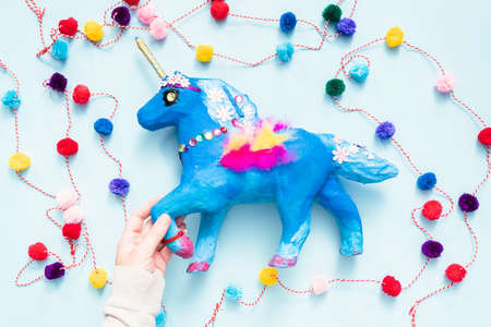 Kids craft. Painted blue and decorated with jewels and feathers paper mache unicorn. Фото со стока