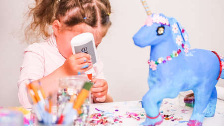 Little girl decorating paper mache unicorn with jewels and paper flowers.