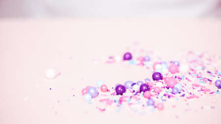 Colorful purple sprinkle blend on a pink background. 写真素材