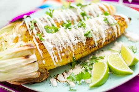 Grilling mexican street corn elote garnished with spices and fresh cilantro on a serving plate. 스톡 콘텐츠