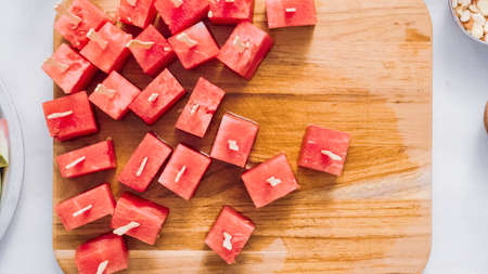 Slicing watermelon into cubes for preparing chocolate covered watermelon bites.