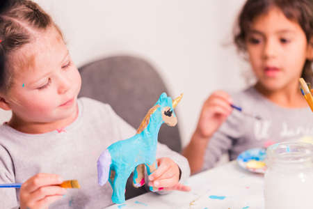 Little girls decorating small paper mache unicorn figurines.