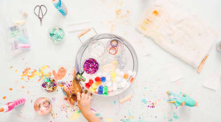 Step by step. Little girls decorating paper mache unicorn with glitter and paper flowers. Stock Photo
