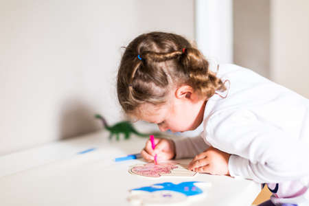 Little girl drawing at her desk at home.