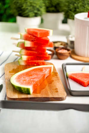 Sliced watermelon in triangle shapes on wooden sticks.