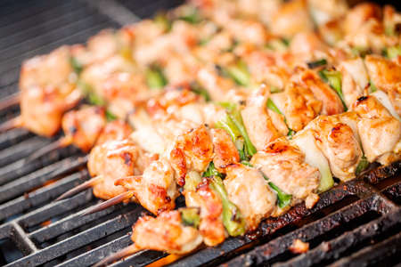 Step by step. Grilling chicken yakitori on bamboo skewers on outdoor gas grill. Stock Photo