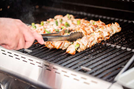 Step by step. Grilling chicken yakitori on bamboo skewers on outdoor gas grill. Banco de Imagens